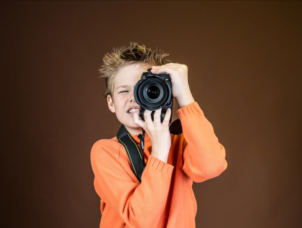 A young man is holding a professional camera and taking a photo