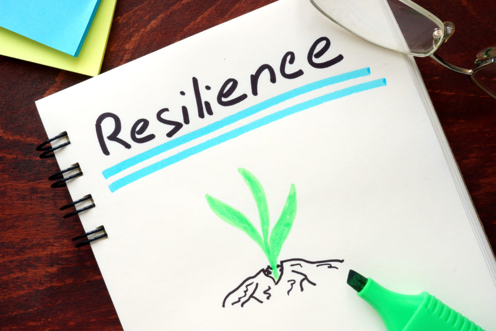 A notebook with the word Resilience written on it and underlined with a highlighter with a drawing of a plant shoot pushing up through a crack in some soil