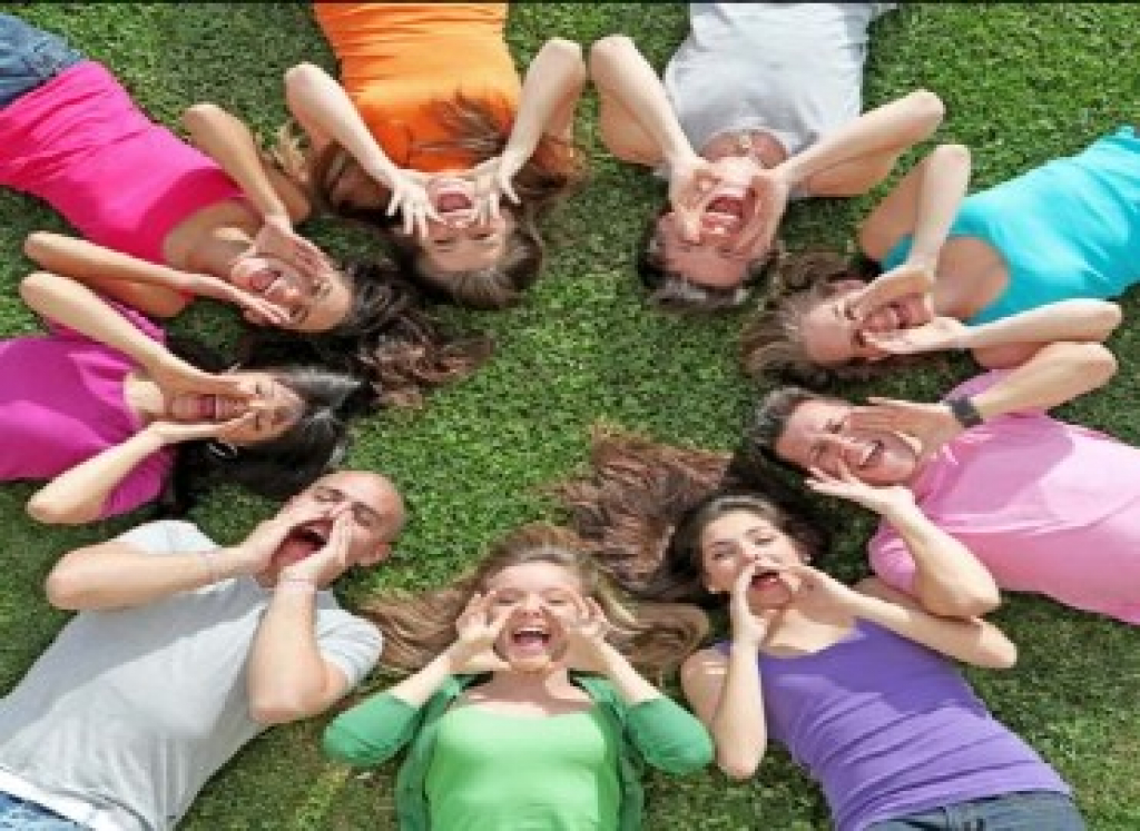 A group of young people laying on their backs in a circle with all their heads facing towards the centre of the circle, cupping their mouths with their hands and shouting