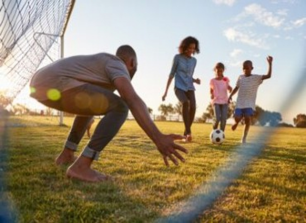A photograph of A family playing football, kicking the ball towards the goal