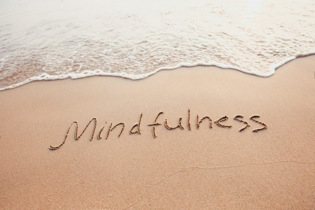 Waves lapping on the shore with the word Mindfullness written in the sand on the beach