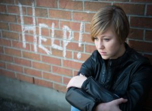 "A young person sat on the floor against a brick wall with the word ""help"" in graffiti next to them"