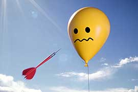 A dart is flying towards a balloon with a worried face on it