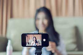 A young woman is filming herself giving make-up tutorials using a smartphone on a tripod