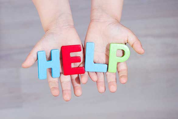 A pair of hands holding cutout wooden letters spelling out the word HELP
