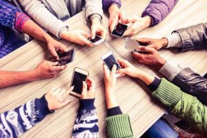 A group of people in a circle checking their smartphones