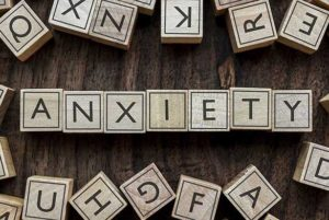 Wooden letter blocks on a table spelling out the word ANXIETY