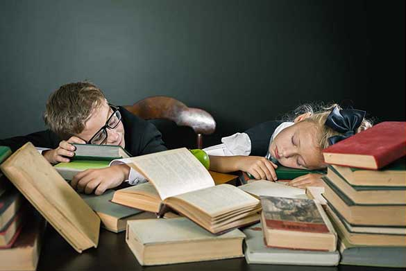 A desk with books scattered across it with two young adults sleeping with their heads resting on the books
