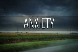 The word ANXIETY on a landscape background