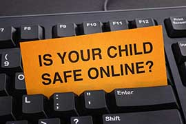 A keyboard with a note stuck between they keys with the phrase IS YOUR CHILD SAFE ONLINE? on it