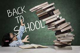 A tall stack of books on a desk is falling towards a young adult who is sat in front of a blackboard with the words BACK TO SCHOOL written on it