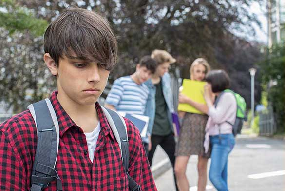 A photo where a young man who looks sad is separated from a group of young people who seem to be talking about him behind his back