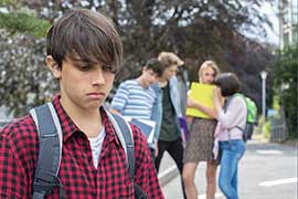 A young man who looks sad is separated from a group of young people who are talking about him behind his back