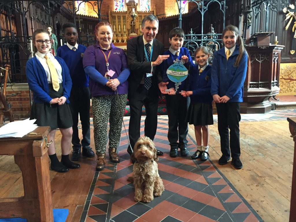 Staff, pupils and Winnie the school dog from St Peter's primary school are presented with the Kent Award by Councillor Rory Love. The presentation is within St Peter's Church.