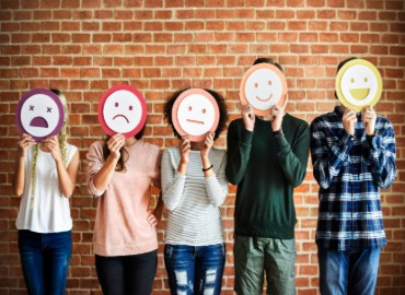 Young people against a brick wall with cartoon faces featuring different emotions covering their own faces
