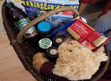 A hamper filled with a teddy bear, food, magazine and crafts