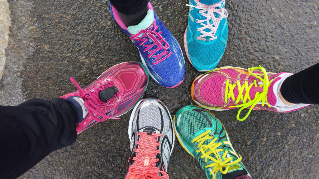 bird's eye view of six people's feet in bright coloured trainers