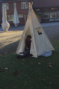 a primary school child in a teepee tent on school field playground in front of the school building