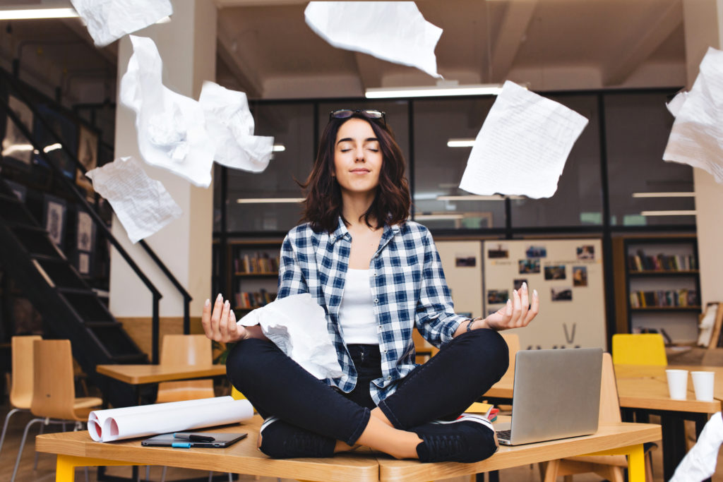 teenage girl sitting cross-legged on a school desk in a classroom meditating with papers flying all around her