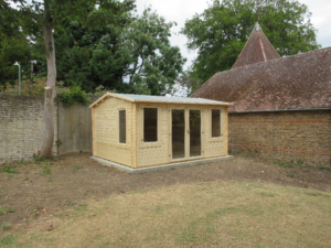 a grassed garden and log cabin in the middle