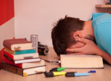 A boy with his head in his hands on his desk surrounded by text books
