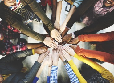 A photo of staff hands all together in a circle from above