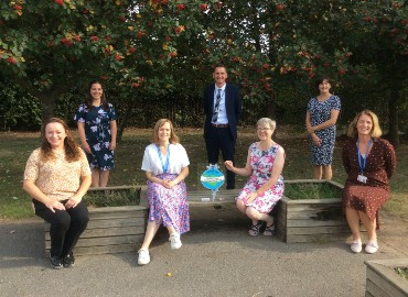 Photo of Coxheath primary school and HeadStart staff members outside sitting on benches displaying the Kent Award