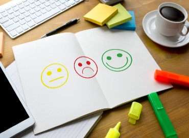 Printed smiley faces surrounded by highlighter pens, post-it notes and a cup of coffee