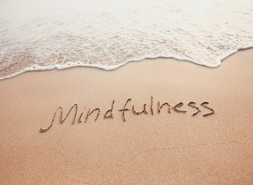 Sand on the beach with the word mindfulness written on the sand