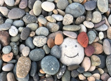 A photograph of pebbles with one largish pebble having a smiley face drawn on it.