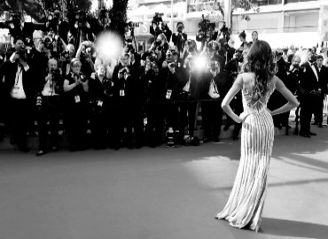 Black and white photo of a celebrity posing in front of a wall of paparazzi