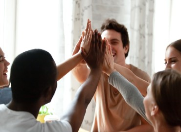 A photo of a group of young people high-fiving