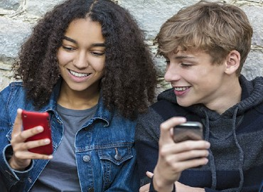 A photograph of 2 young people looking at their phones