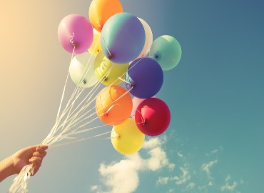 A photo of blue sky and white clouds, and a big bunch of multi-coloured balloons flying in the air being held together with a bundle of string that is being held by a hand coming up from the bottom left corner of the image.