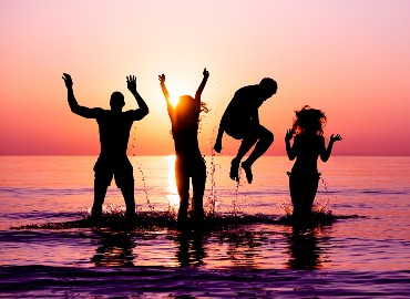 A photo of four silhouetted teenagers jumping up in the sea, where the sky is pink, purple and orange reflected in the sea.