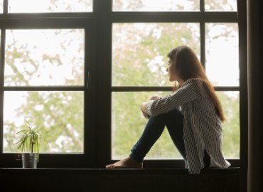 A girl sitting on a windowsill alone looking out of the window