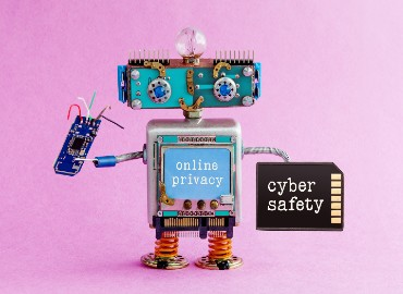A robot made up of computer parts smiling, holding a microchip that has 'cyber safety' written on it