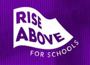 Rise above logo - a purple background with a white flag waving in the middle with the words 'Rise Above' in purple, and underneath the flaf in white are the words 'for schools'