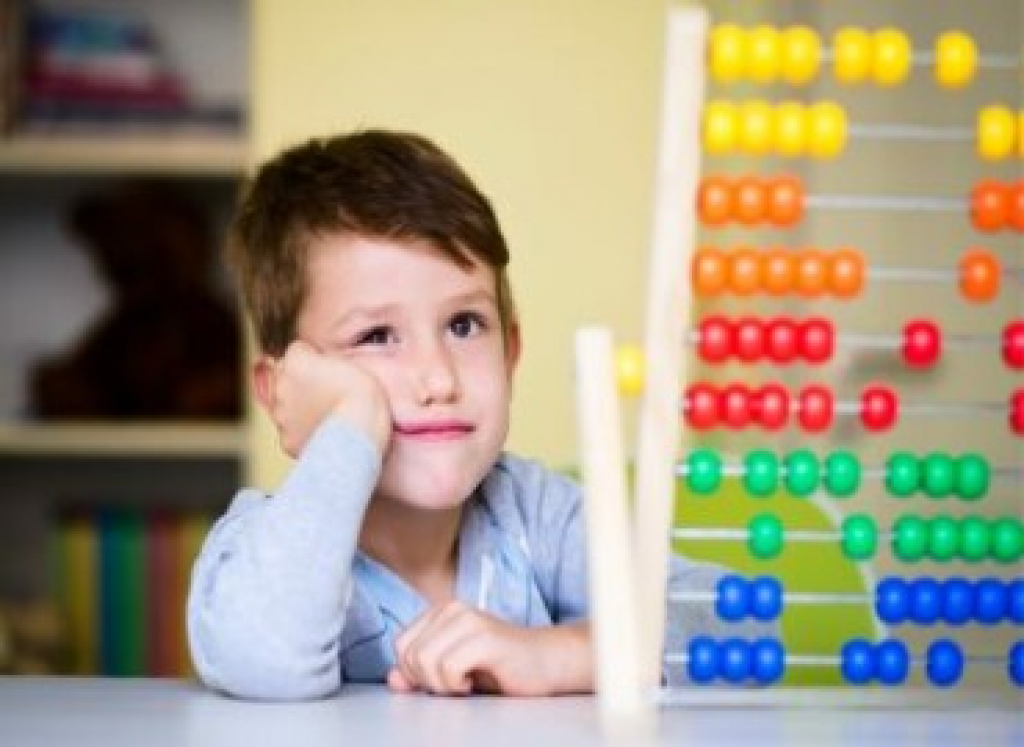 boy with abacus looking frustrated with face resting on hand, elbow on table