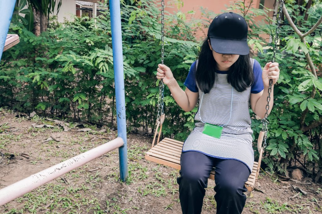 teenage girl sitting alone on a swing with cap covering her face