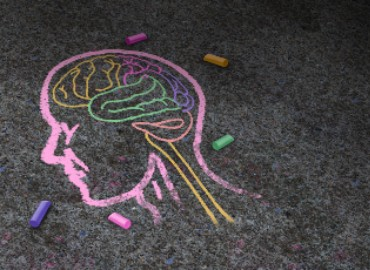 An image of concrete pavement, with multi-coloured chalk-drawn image of a human head and a brain inside. Coloured chalk blocks left on the ground around the drawing.