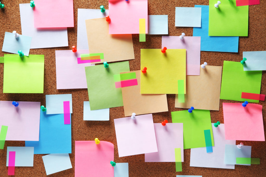 A brown cork-board background with a variety of colourful post-it notes stuck to the board with colourful pins