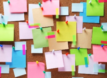A pin board covered in colourful post it notes and pins
