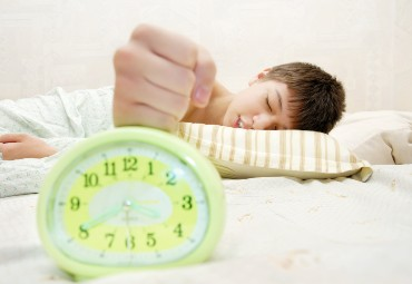 Alarm clock in the foreground with a sleeping boy in the background who is reaching out to turn off the alarm clock