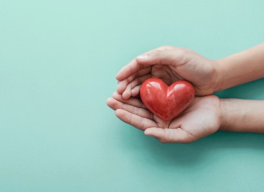 Light blue background with a pair of hands on the right, holding a red heart