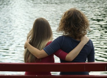 A photograph of two people from behind, sitting on a bench with their arms round each other, looking at some water in front of them.